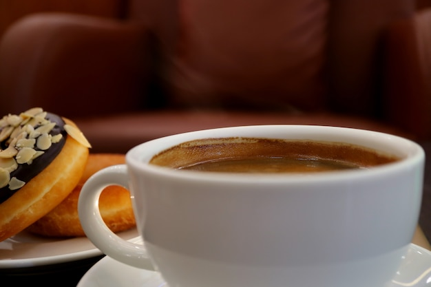 White cup of hot coffee with light smoke, blurred doughnuts and armchair in background