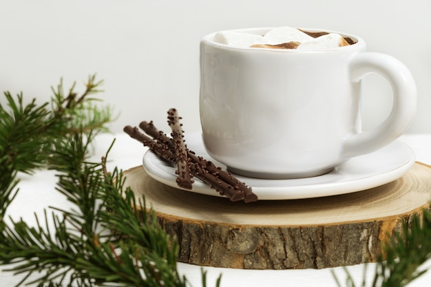 White cup of hot coffee with marshmallows and chocolate sticks
