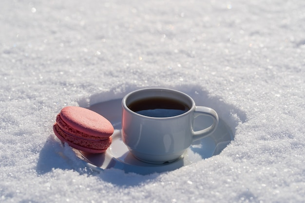 White cup of hot coffee with pink macaroon on a bed of snow and white background, close up. concept of christmas winter morning