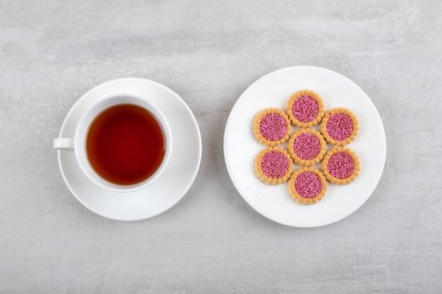 Una tazza bianca di tè caldo e biscotti con spruzza su un piatto bianco.