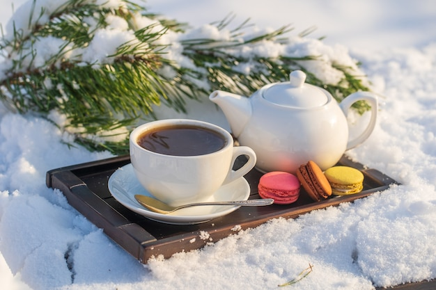 White cup of hot tea and teapot on a bed of snow and white background, close up. concept of christmas winter morning