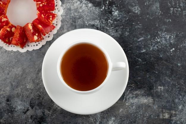 Una tazza bianca di tè caldo con il dessert affettato.