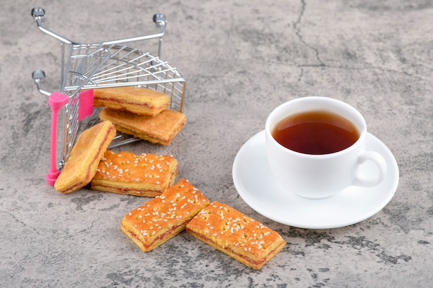 A white cup of hot tea with sweet pastries placed on a stone table.