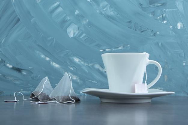 Una tazza bianca di tè caldo con bustine di tè.