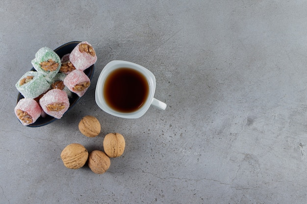 A white cup of hot tea with traditional turkish delights and healthy walnuts