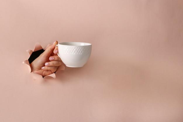 분홍색 종이 배경, 커피 타임, 복사 공간에 둥근 구멍을 통해 여성의 손에 흰색 컵