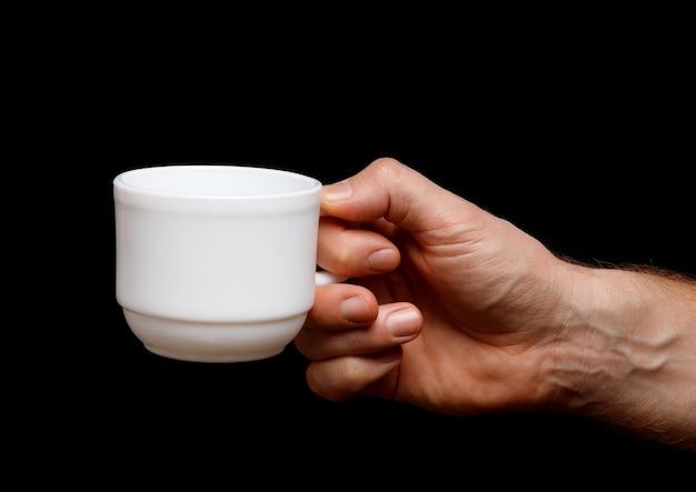 手に白いカップ