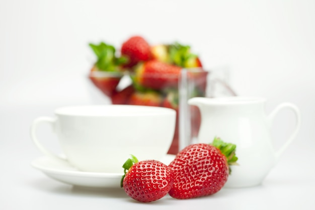 White cup and milk jug with strawberries isolated on white