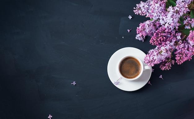Белая чашка ароматного кофе эспрессо на темном каменном столе, цветущие ветви фиолетовой сирени, копировальное пространство