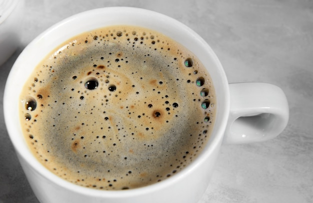 위에서 블랙 커피의 흰색 컵입니다. 커피 거품의 상위 뷰를 닫습니다.