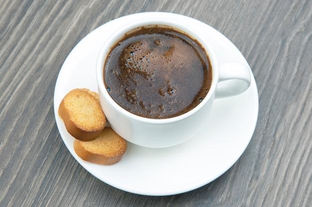 木製フレームにビスケットとブラックコーヒーの白いカップ
