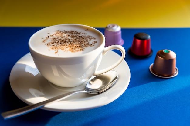 흰색 카푸치노 컵, 에스프레소 커피는 파란색 배경에 캡슐과 꼬투리와 함께 제공됩니다. 측면보기. 커피 머신용 음료 캡슐