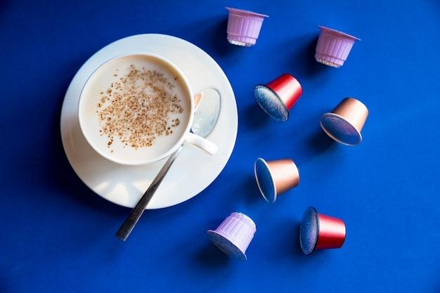 흰색 카푸치노 컵, 에스프레소 커피는 파란색 배경에 캡슐과 꼬투리와 함께 제공됩니다. 평면도. 커피 머신용 음료 캡슐
