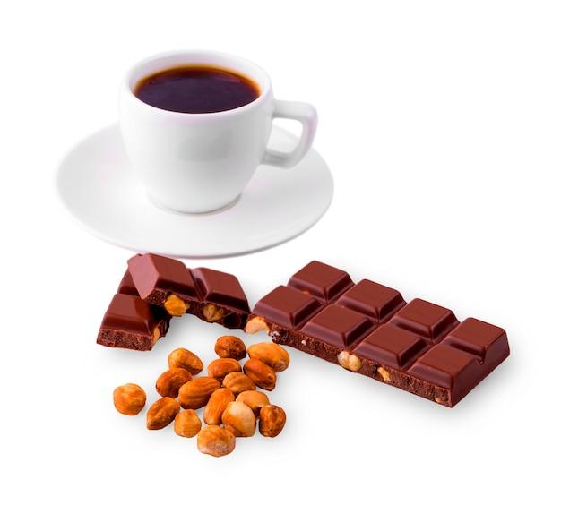 白い背景の上のナッツとコーヒーとチョコレートの白いカップ