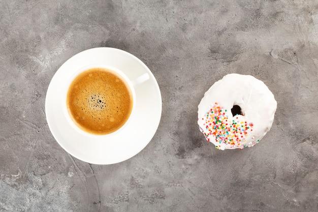 白いカップのコーヒーと白いアイシングと灰色の背景に色とりどりの砂糖ペストリーのドーナツ。フラットレイ