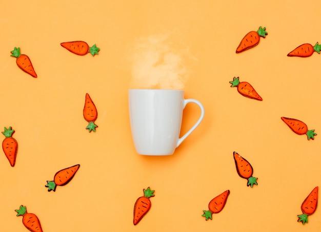 黄色のコーヒーとイースタークッキーのニンジンの白いカップ
