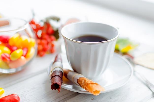 Белая чашка кофе и фруктовые кожаные роллы и чипсы на завтрак