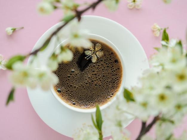 ピンクのテーブルの上のコーヒーと春の花の花の白いカップ。朝のロマンチックなアメリカーノ。カフェ&バー、バリスタアートコンセプト。上面図。フラットレイ