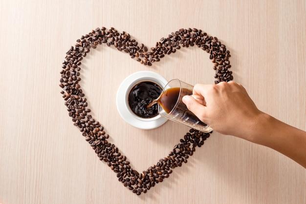 木製の表面にコーヒー豆の白いカップ