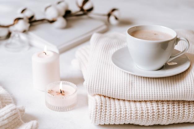 Белая чашка кофе, хлопок, свечи.