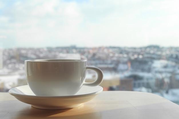 ぼやけた背景のカフェのテーブルに白いコーヒーカップ