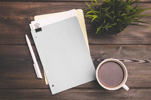 テーブルとメモ帳とクリップオフィス文房具の花の上の白い一杯のコーヒー
