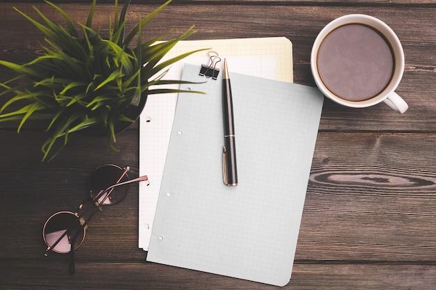 壁に白い一杯のコーヒーとメモ帳とクリップオフィスの文房具の花。