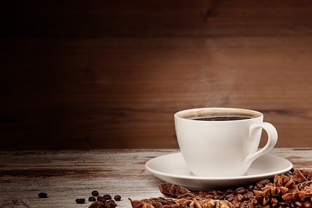 木製の背景の上の白いコーヒーカップ