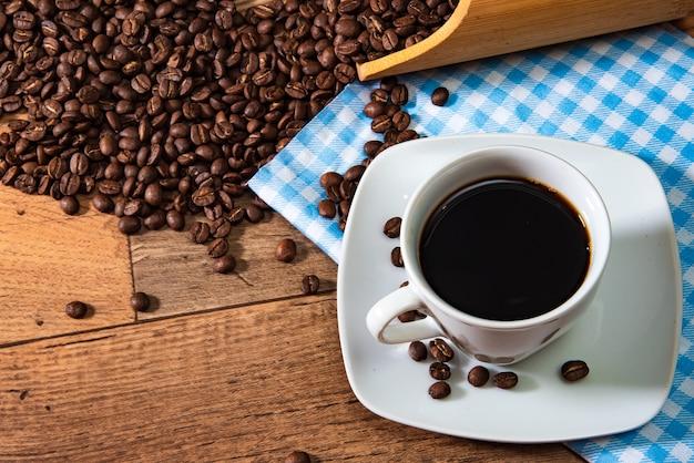 木製の背景に豆とコーヒーの白いカップ