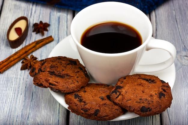 プロヴァンススタイルの軽い木製のテーブルにチョコレートチップクッキーとコーヒーの白いカップ