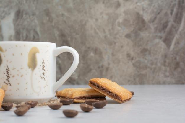 Белая чашка кофе с крекерами и кофейными зернами на белом фоне. фото высокого качества