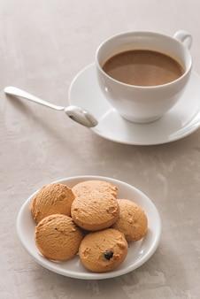 白い背景で隔離のバタークッキーとクリーミーなコーヒーの白いカップ