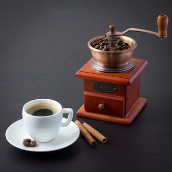 Белая чашка эспрессо и ручная деревянная кофемолка