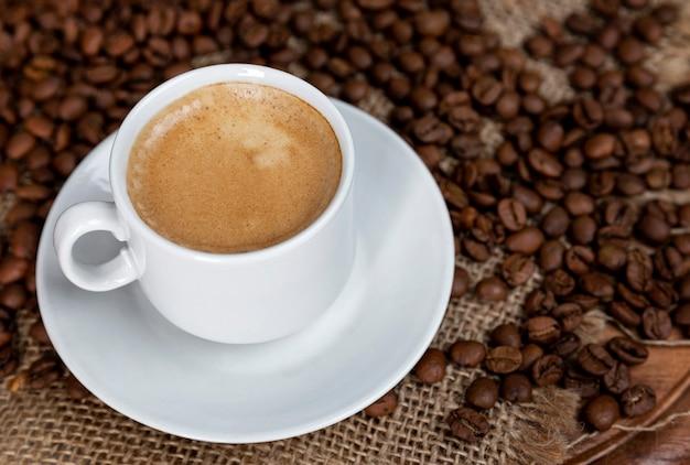 泡立つコーヒーの白いカップと解任に振りかけた豆。