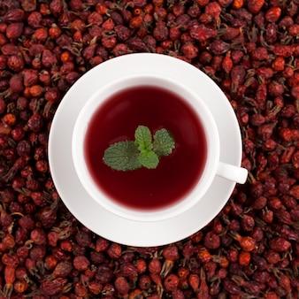 Белая чашка травяного чая из гибискуса и сушеных плодов шиповника на фоне сушеных ягод шиповника.
