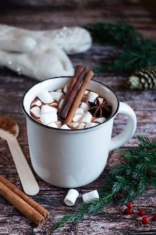 素朴な木製の卓上にマシュマロとスパイスとホットカカオまたはチョコレートの白いカップ