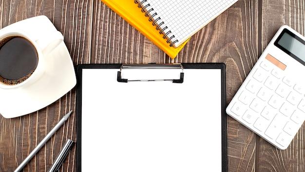 Белая чашка горячего кофе и блокнот и бумага, калькулятор на деревянном столе