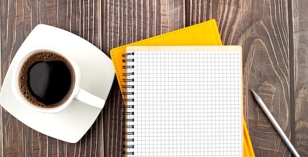 Белая чашка горячего кофе и блокнот на деревянном столе