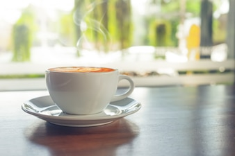 White cup of hot coffee on table in cafe with morning light