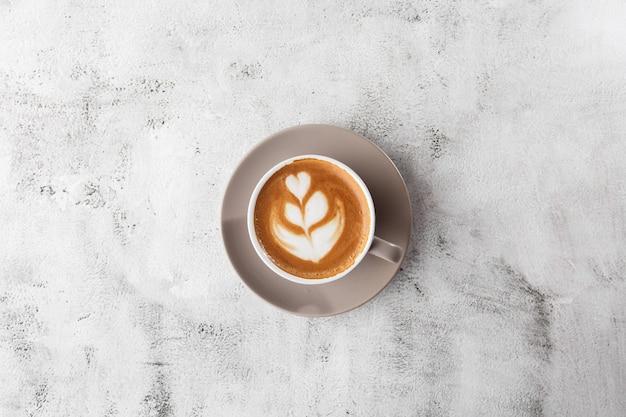 Белая чашка горячего кофе латте с красивой молочной пены текстуры искусства латте, изолированные на светлом фоне мрамора. вид сверху, копирование пространства. реклама для меню кафе. меню кафе. горизонтальное фото.