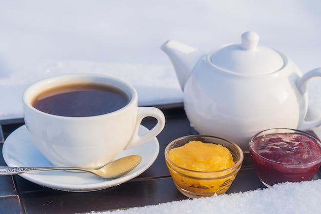 눈과 흰색 배경의 침대에 뜨거운 차와 찻주전자의 흰색 컵을 닫습니다. 크리스마스 겨울 아침의 개념