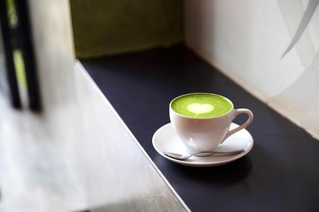 Белая чашка вкусного латте матча с искусством любви. концепция валентина. черный каменный фон.
