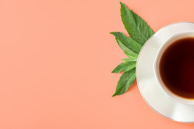 紅茶とソーサーの白いカップは、明るい背景にミントの葉します。ミントと紅茶。上面図。