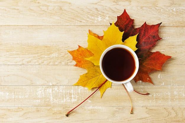 秋のカエデの葉のお茶の白いカップ-木製の背景の上面図