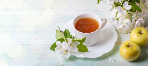 Белая чашка чая на блюдце с ветки яблони цветут и желтые яблоки на деревянных фоне. баннер, копия пространства.