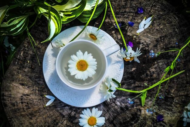 Белая чашка чая с ромашкой на деревянном фоне, летом, рано утром