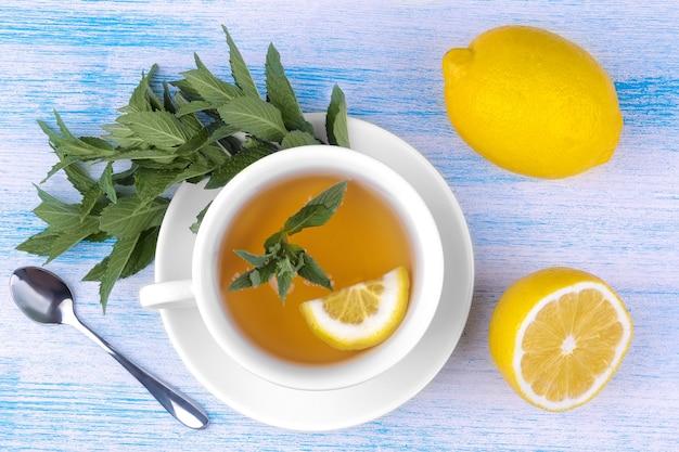 青い木製の背景の上面図にミントとレモンとお茶の白いカップ