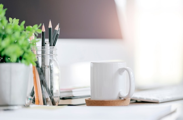 White cup on office desk with bright light background.