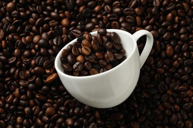 Белая чашка на кофейных зернах, крупным планом