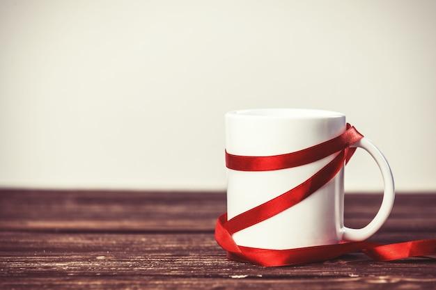 Белая чашка на деревянном столе